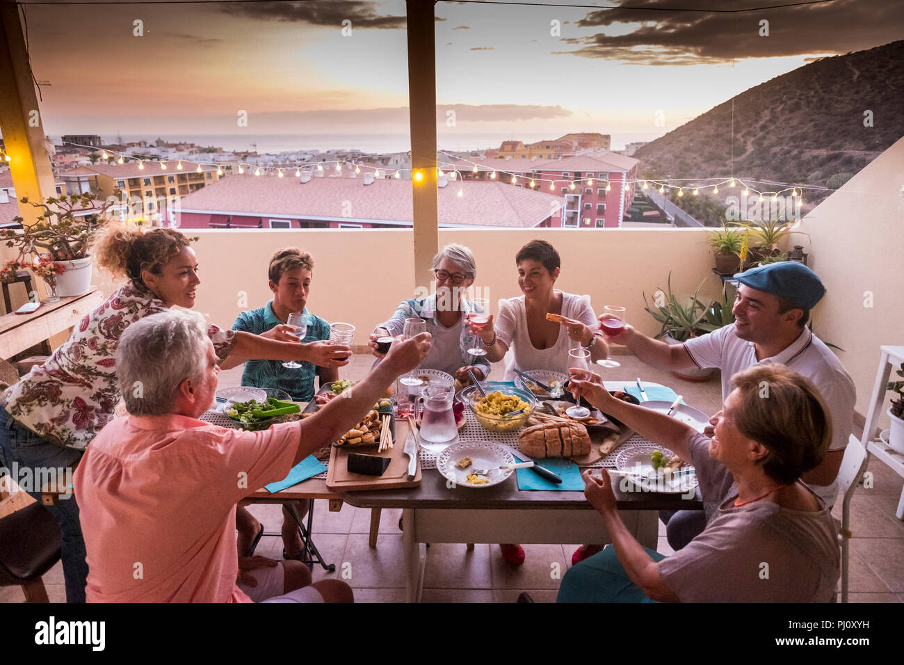 group of friends and parents at home dining together and clinking glasses with beverages. everybody smile and have fun celebrating in friendship. happ - Stock Image