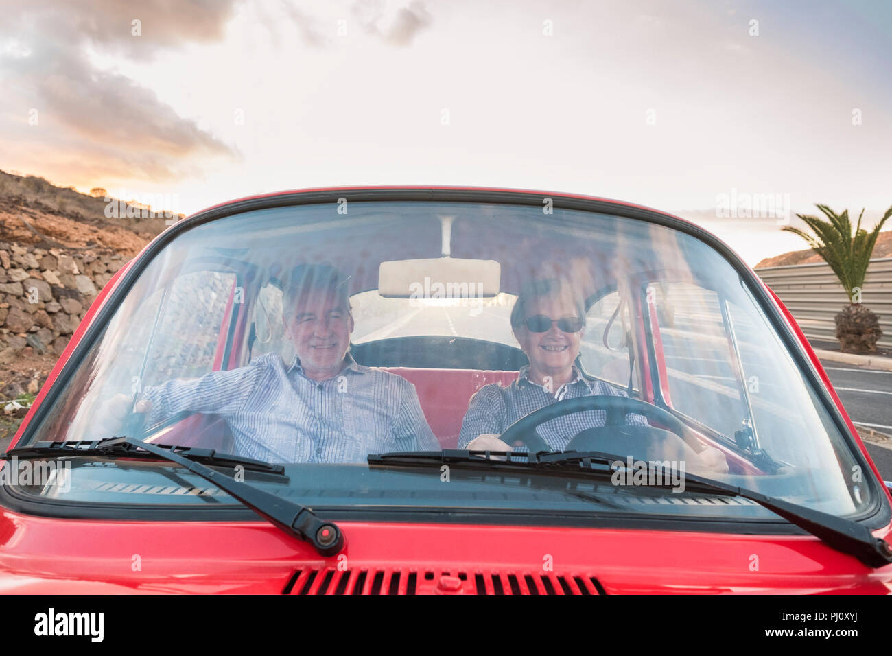 nice adult couple drive and love inside a red old vintage car parked on the road. smiles and have fun traveling together. happiness and lifestyle for  - Stock Image