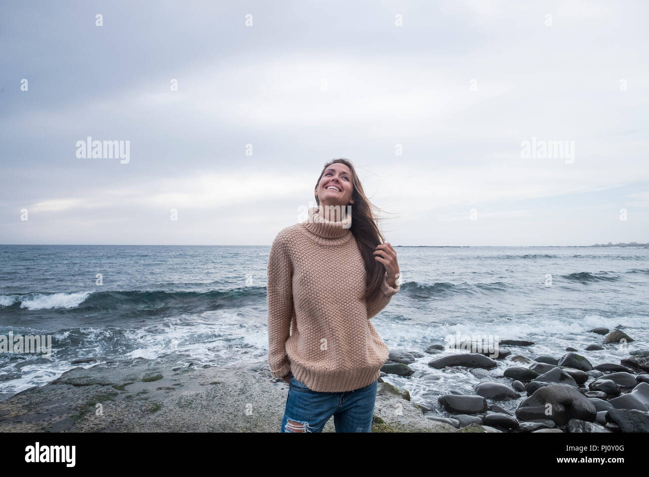 cheerful babe standing at the beach on a wild rock with waves and blue water horizon in the background. freedom lifestyle concept for people love trav - Stock Image