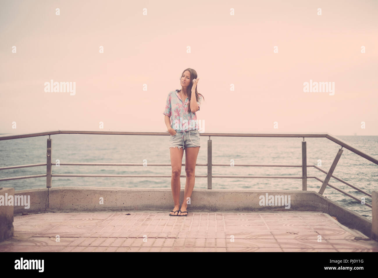 beautiful young lady caucasian woman standing at the beach on the road listening music with headphone and enjoying the leisure activity. vacation and  - Stock Image