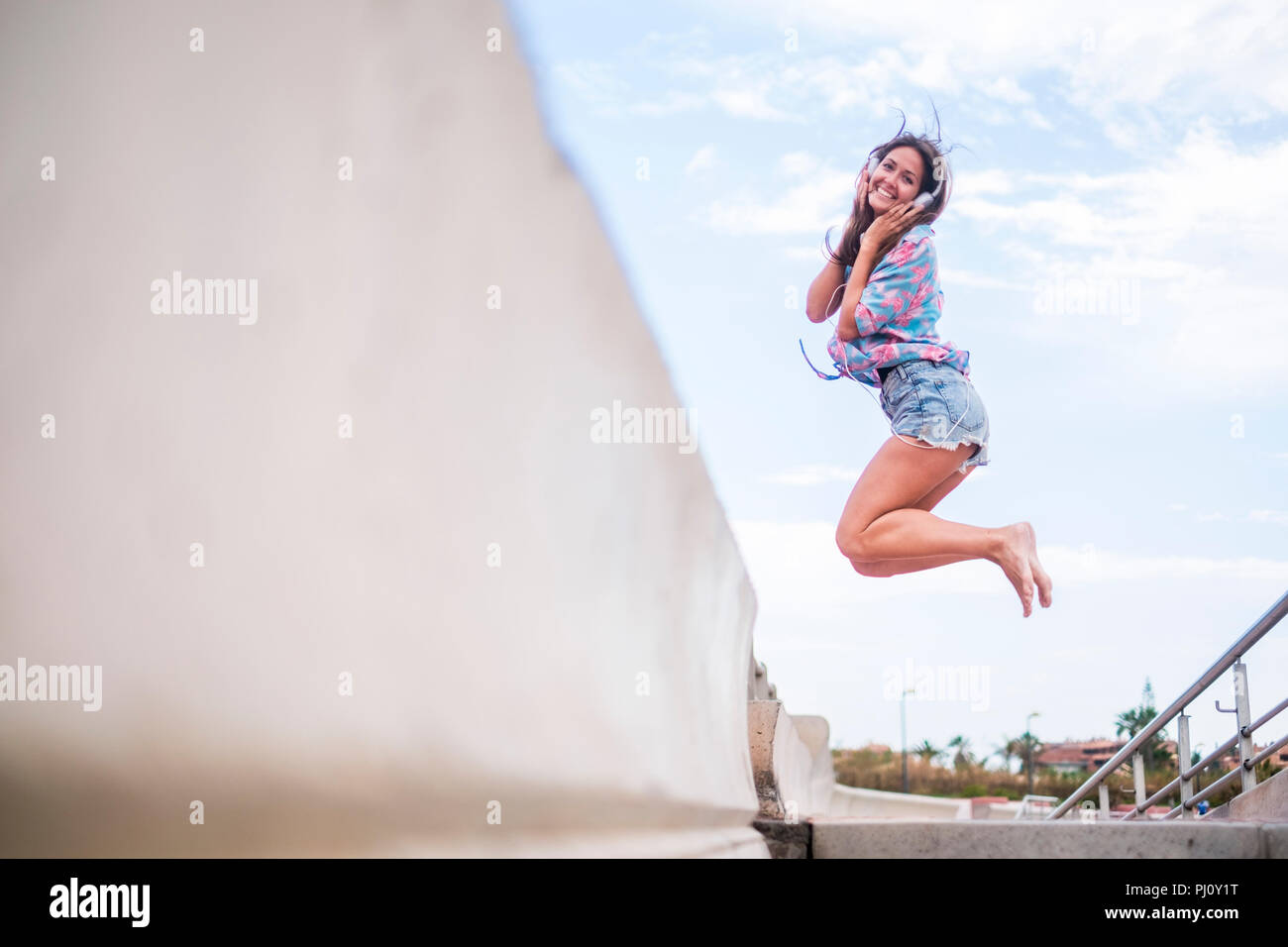 Happiness concept with young beautiful girl jumping with joyful against a white sky blue background. sea side place. Cheerful caucasian woman smile an - Stock Image