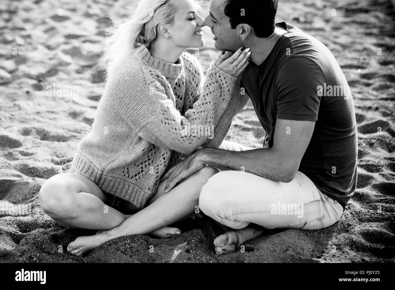 beautiful model couple caucasian young lady and man stay in love hugging and sitting on the beach. blonde and black hair in relationship outdoor leisu - Stock Image