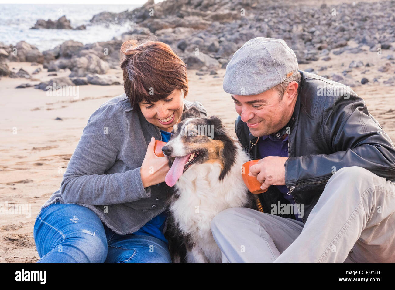 nice group of dog, man and woman young people having fun together at the beach drinking tea and enjoying the outdoor leisure activity. fashion people  - Stock Image