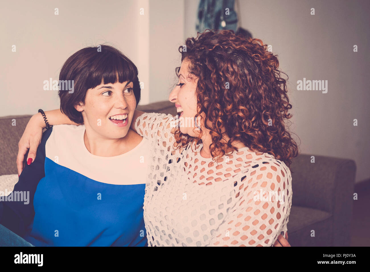 nice time and happiness with laugh and smiles for two caucasian friends lay down together on the sofa at home. friendship concept for indoor picture w - Stock Image
