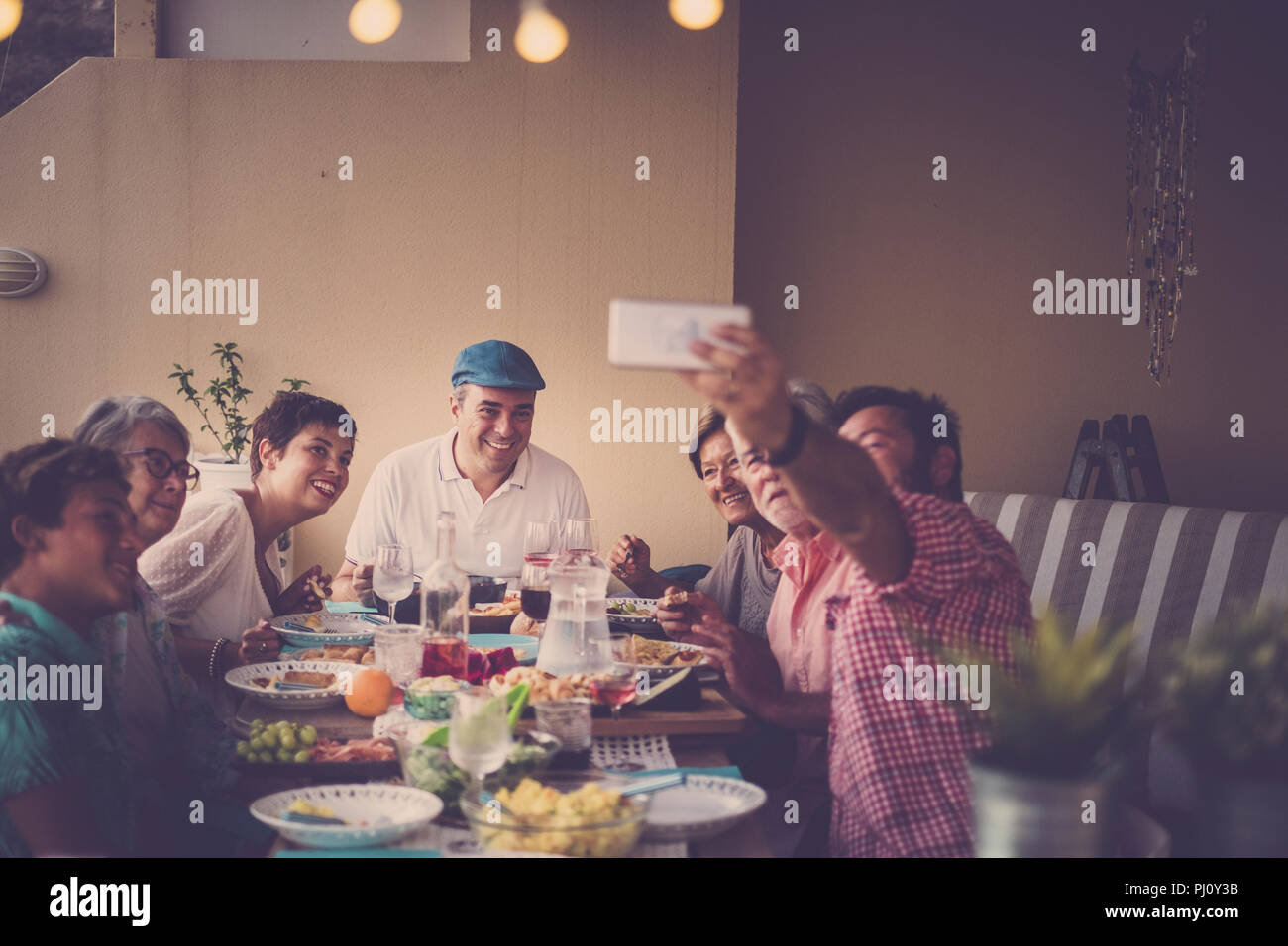 happy group of people in family friendship all together celebrating and having an outdoor nice dinner at home in the terrace. a man take selfie for al - Stock Image