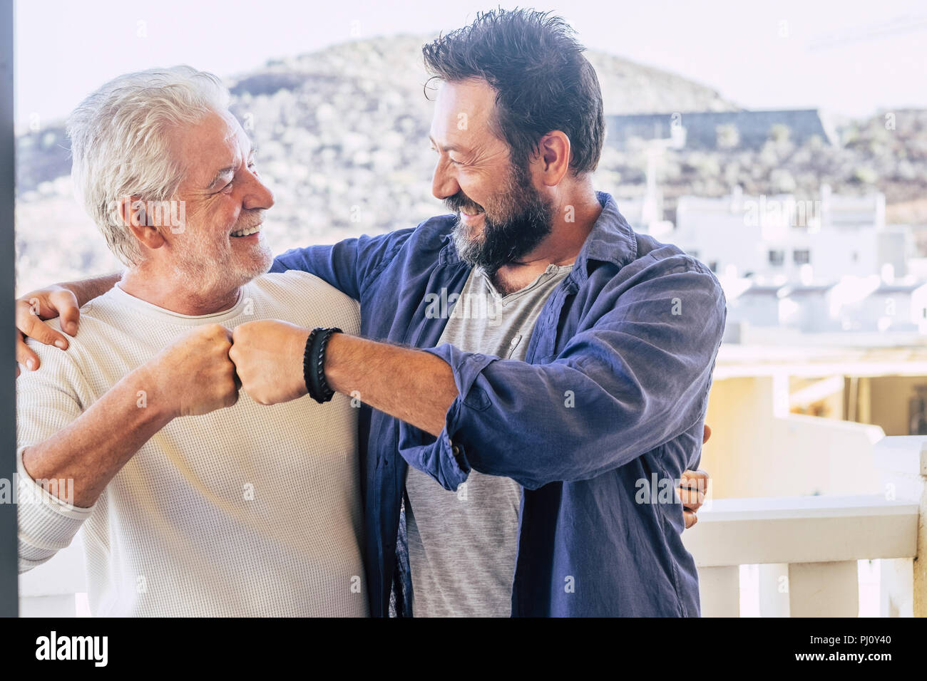 Two happy male friends father and son having a good time together giving friendly punch eachother. city and mountains in background. caucasian people  - Stock Image