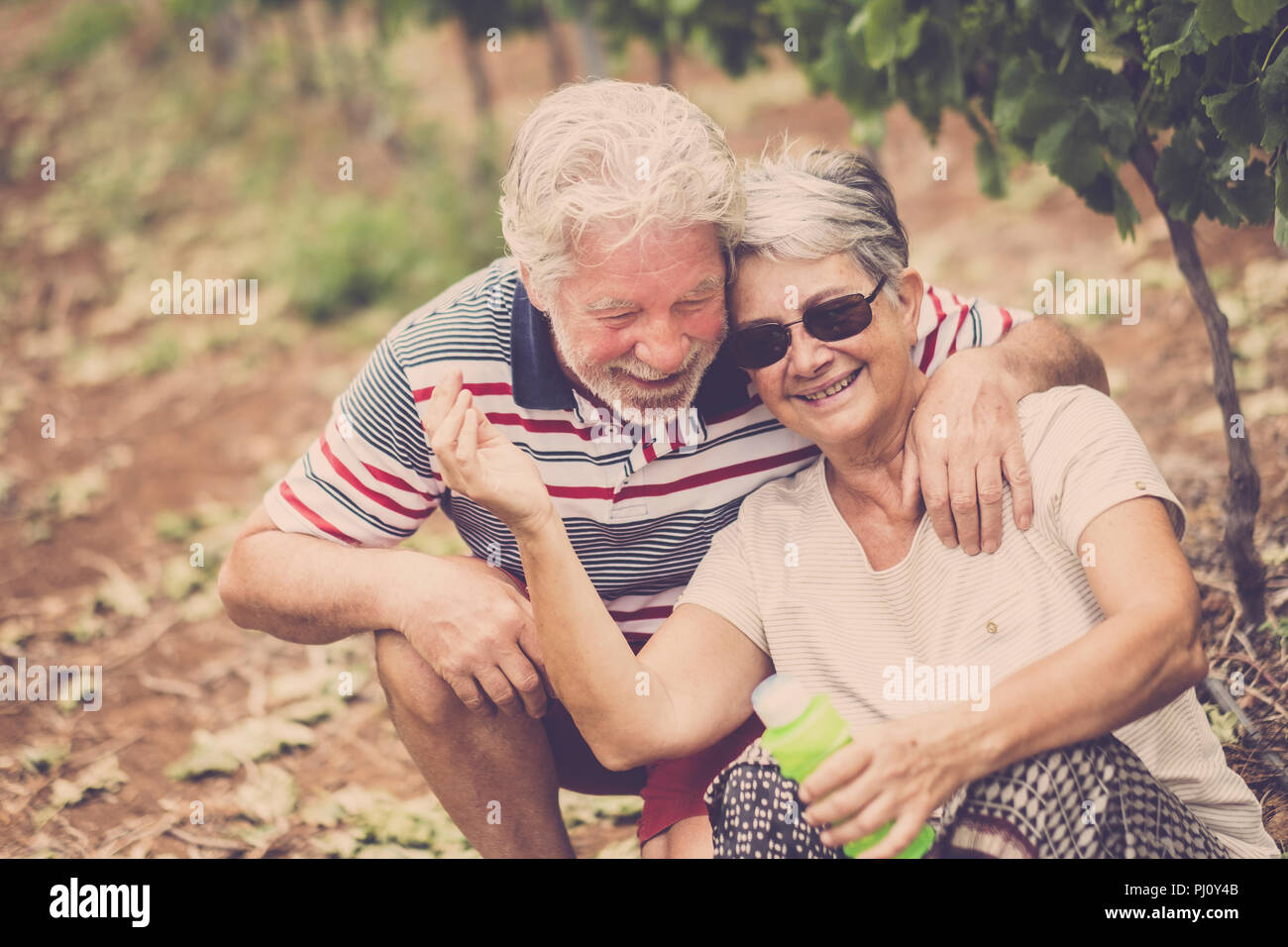 senior adult couple laugh in happines together forever playing with soap bubbles in the country yard outdoor leisure activity. stay young concept and  - Stock Image