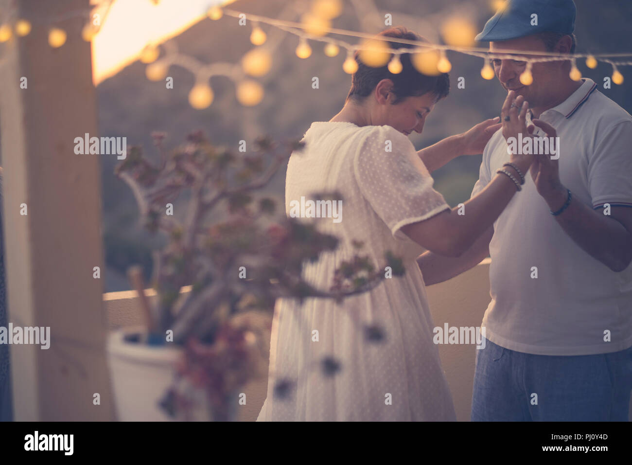 romantic couple dance together with love and romance during the down in the evening at home in the terrace. outdoor leisure activity for middle age wo - Stock Image