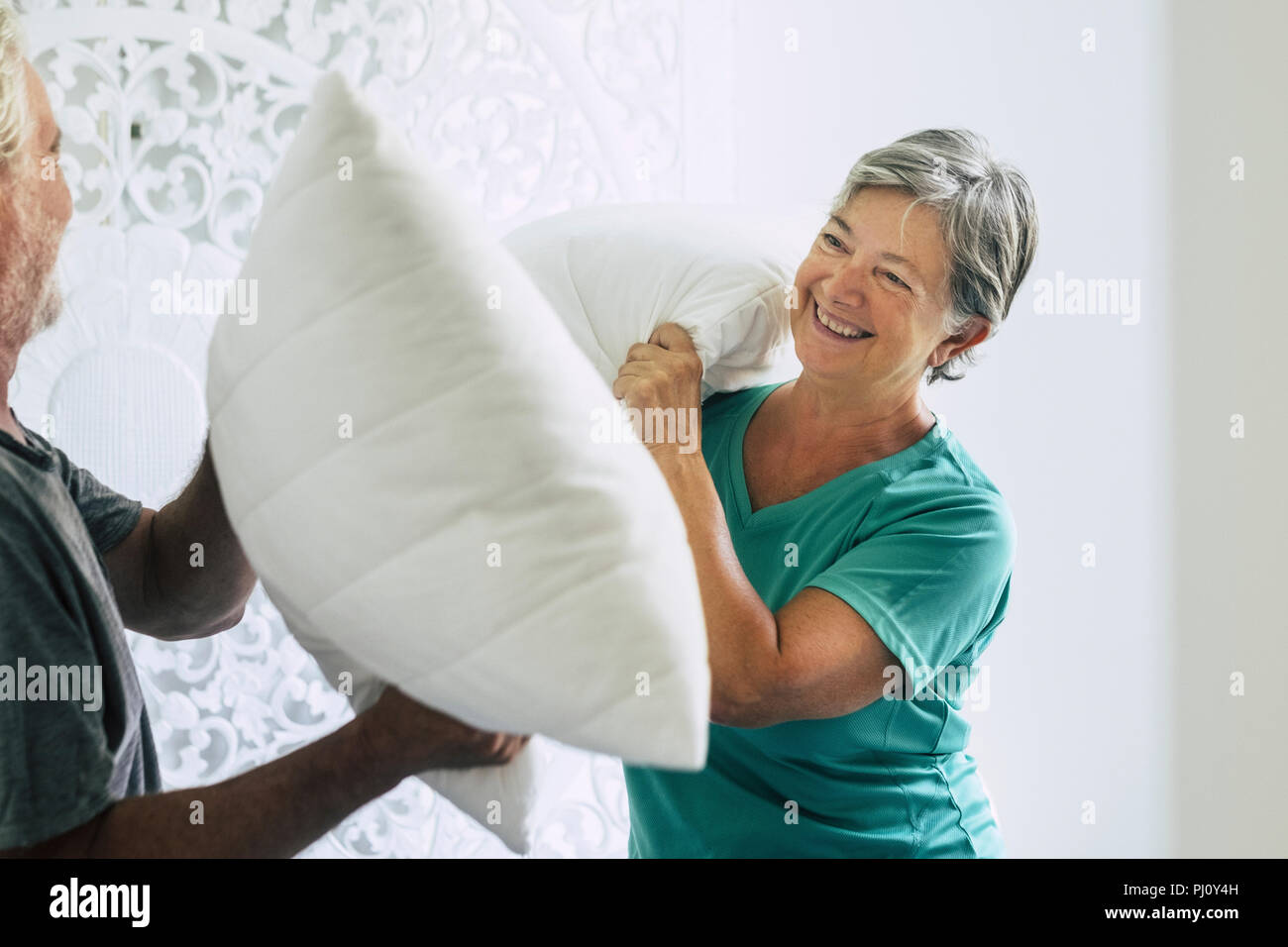 pillows war at home for caucasian couple of playful adult senior man and woman play in the bedroom at the morning. hapiness and joy together forever s - Stock Image