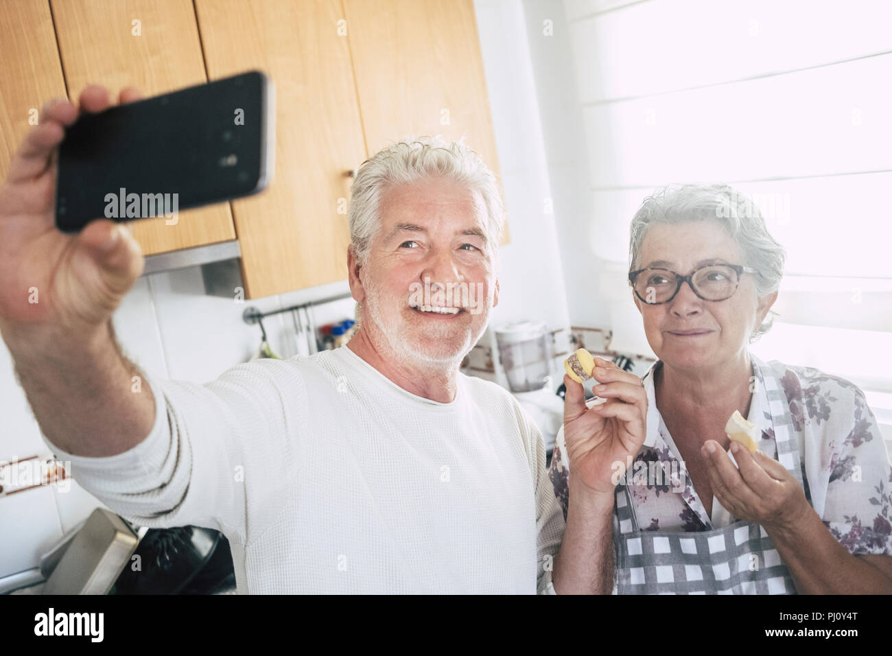 senior adult caucasian happy couple at home in the kitchen cooking and working together with joy and happiness. taking selfie with modern smart phone  Stock Photo