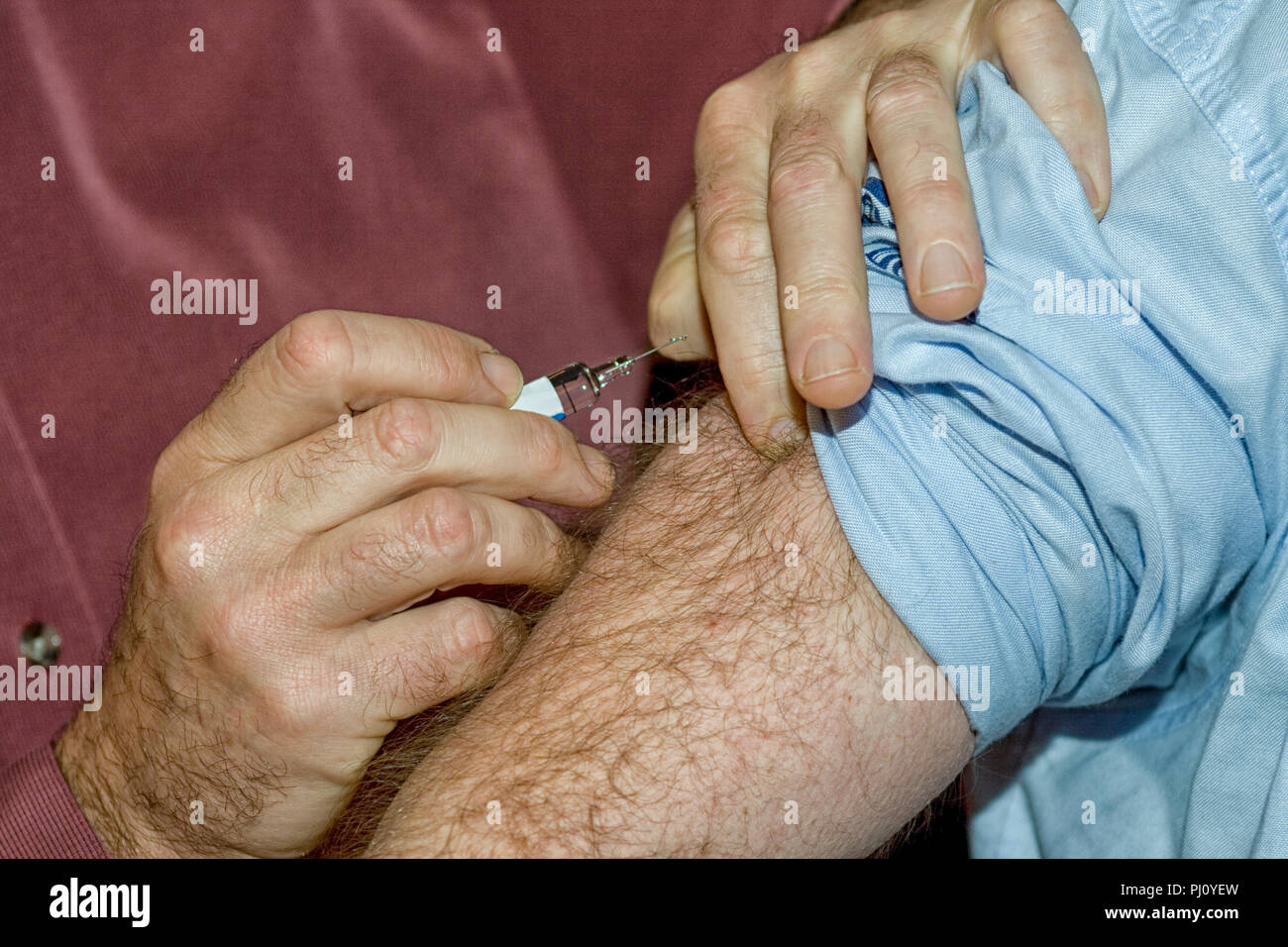 Doctor puts syringe in male hairy arm - Stock Image