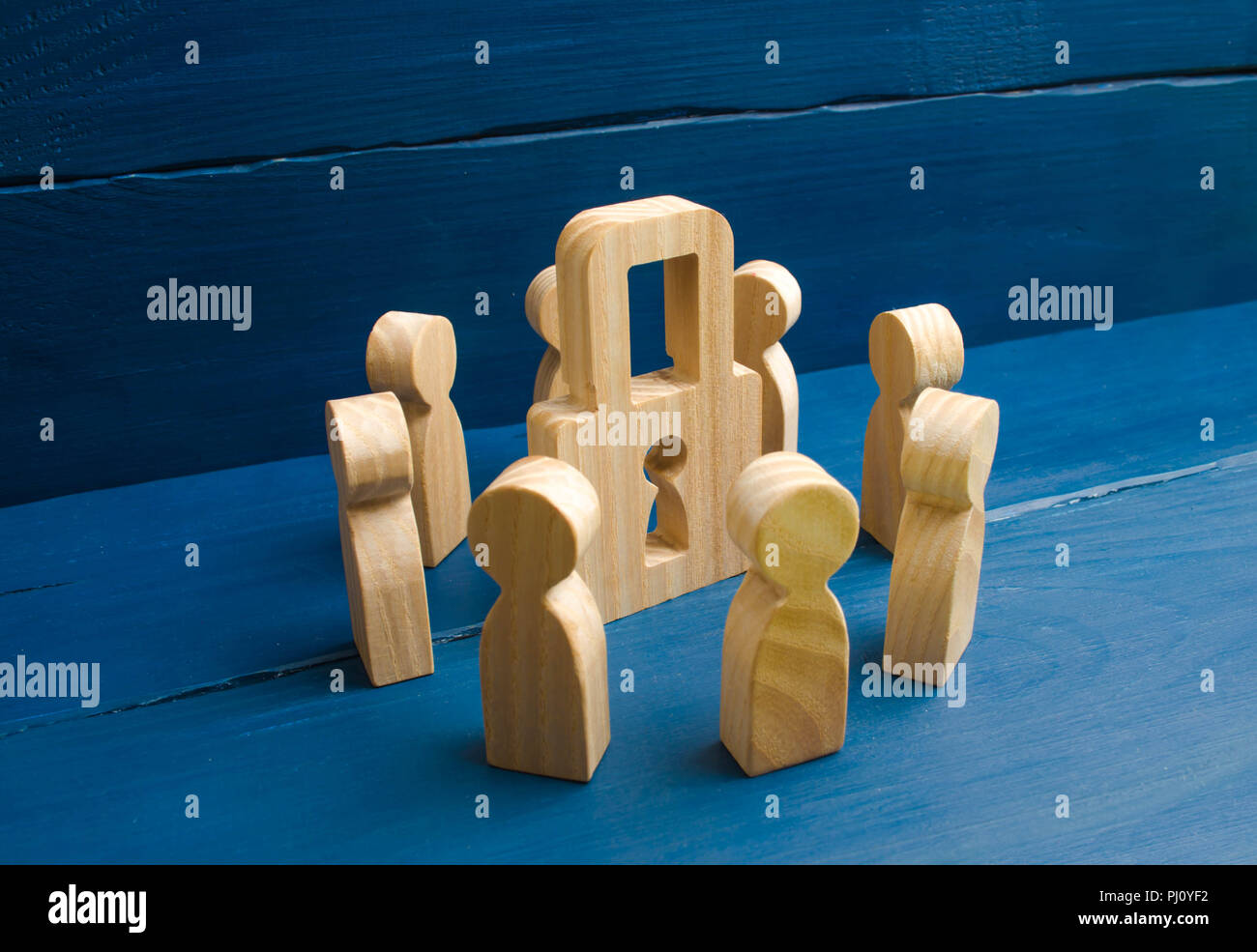 Bank secrecy, medical secret. Wooden figures of people stand around a padlock on a blue background. The concept of security and security, the protecti Stock Photo