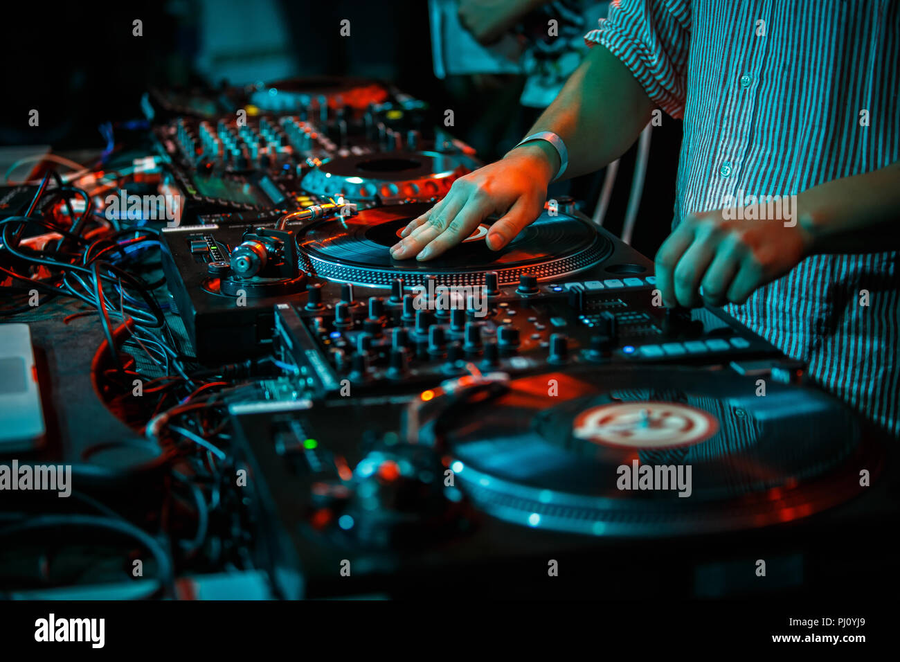 Party dj scratches vinyl record with music on turn table record player in nightclub.Professional club disc jockey scratches records & plays musical se - Stock Image