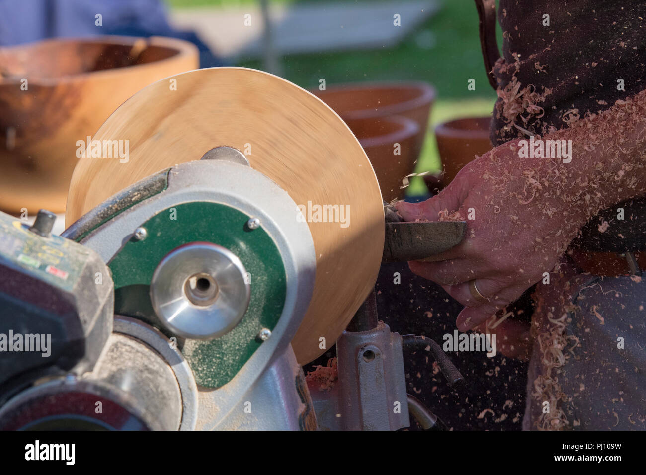 a craftsman wood turning using a lathe to shape wood in a workshop. - Stock Image