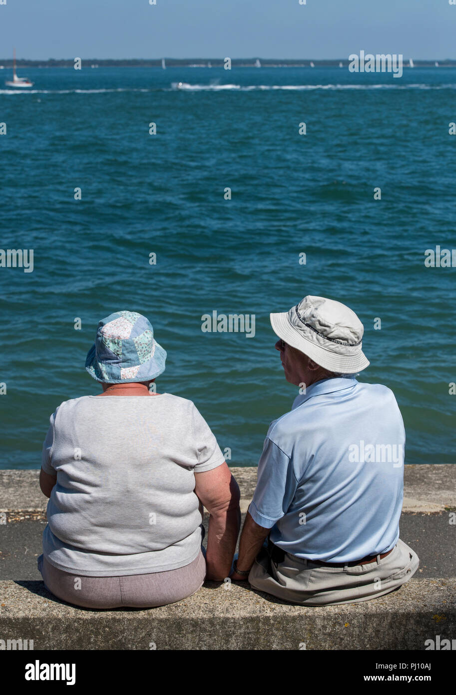 an elderly couple wearing sun hats sitting on a wall at the seaside watching the boats and the sea on holiday. - Stock Image