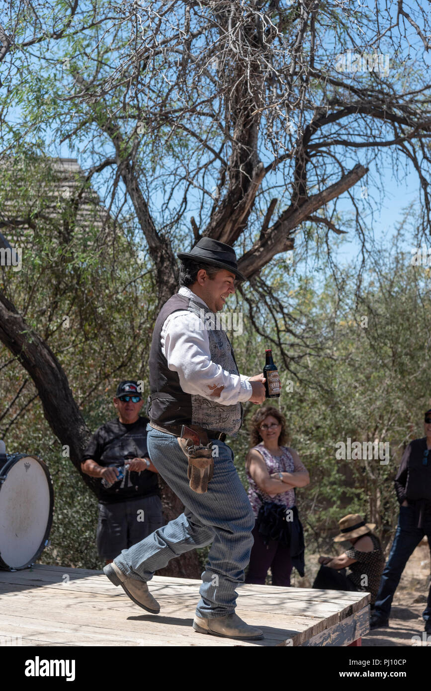 Old west medicine show with actor holding a bottle of elixir and showing it to the crowd. - Stock Image