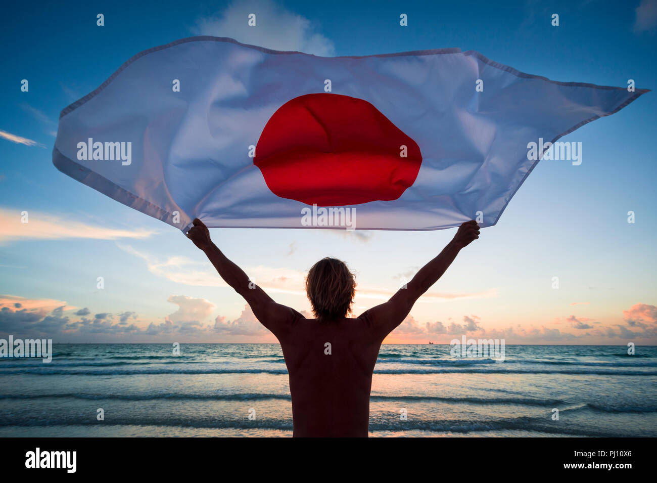 Man holding a fluttering iconic Japanese flag with circle of stars on beach at sunrise - Stock Image