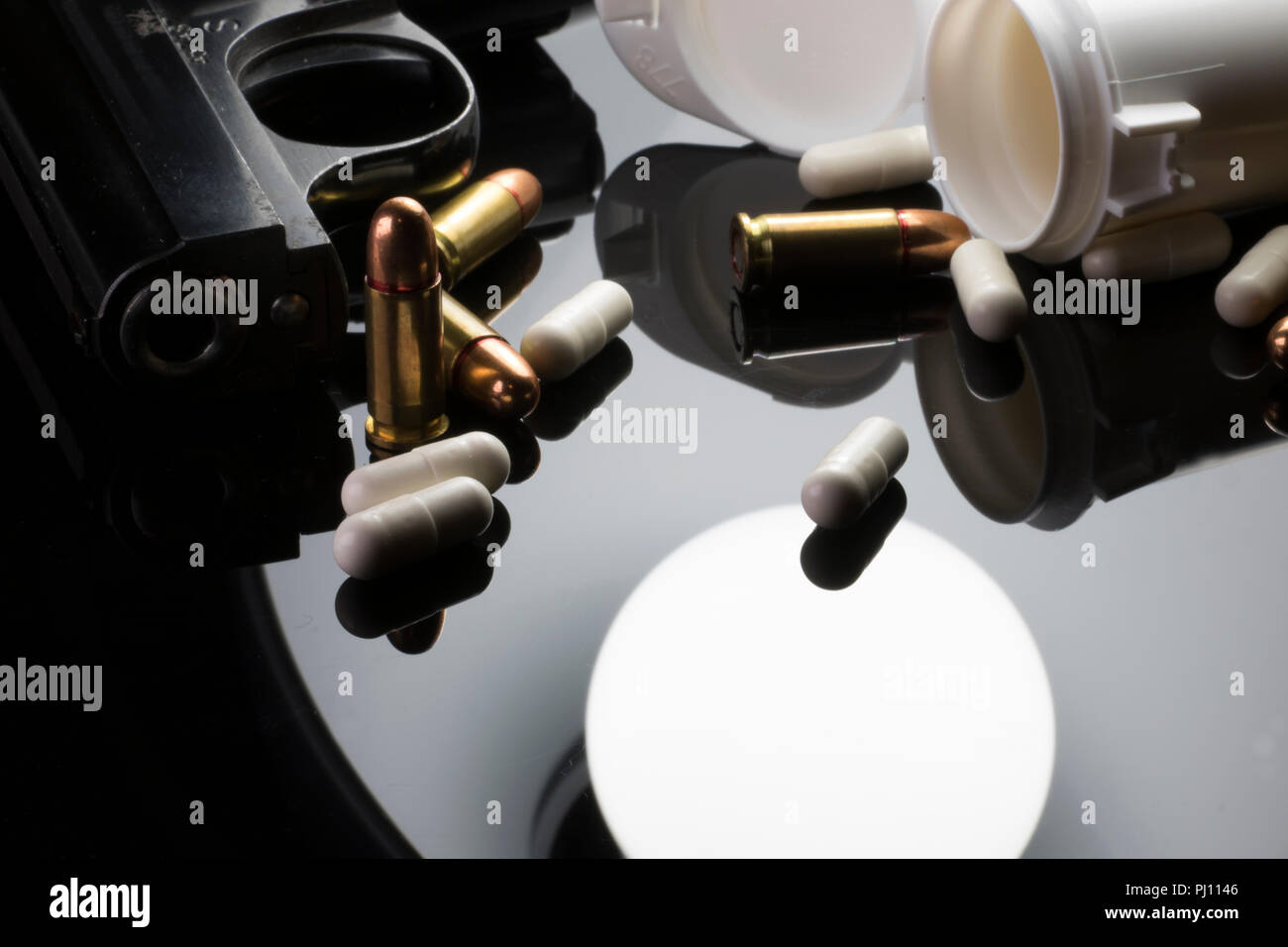 Gun Bullets and White Pills on a black table. - Stock Image