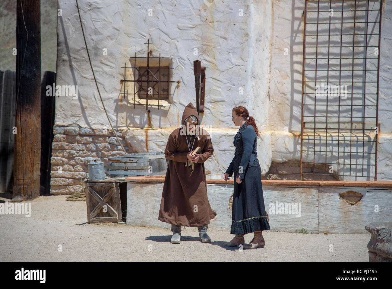 Priest and woman (actors) performing outside at Old Tucson movie studios. - Stock Image
