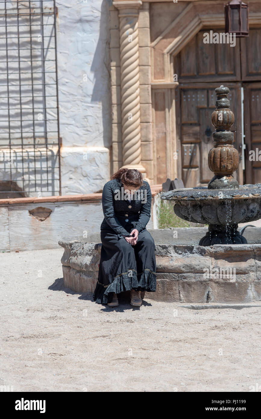 Actress weeping at the well in Old Tucson movie studios. - Stock Image