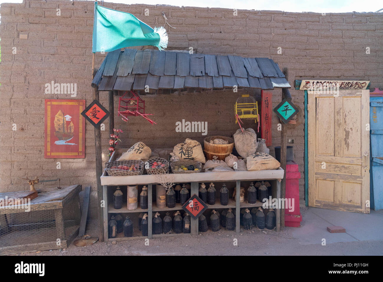 """Old Tucson movie studios back alley, with wooden stand displays various Chinese bags of goods, wooden door with sign reading """"Dragon Fire"""" Adobe brick. - Stock Image"""