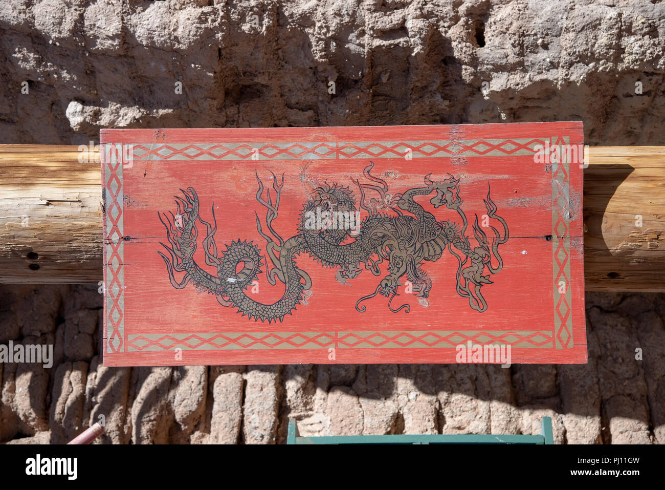 Chinese dragon painted on wooden sign with red, black and gold paint. - Stock Image