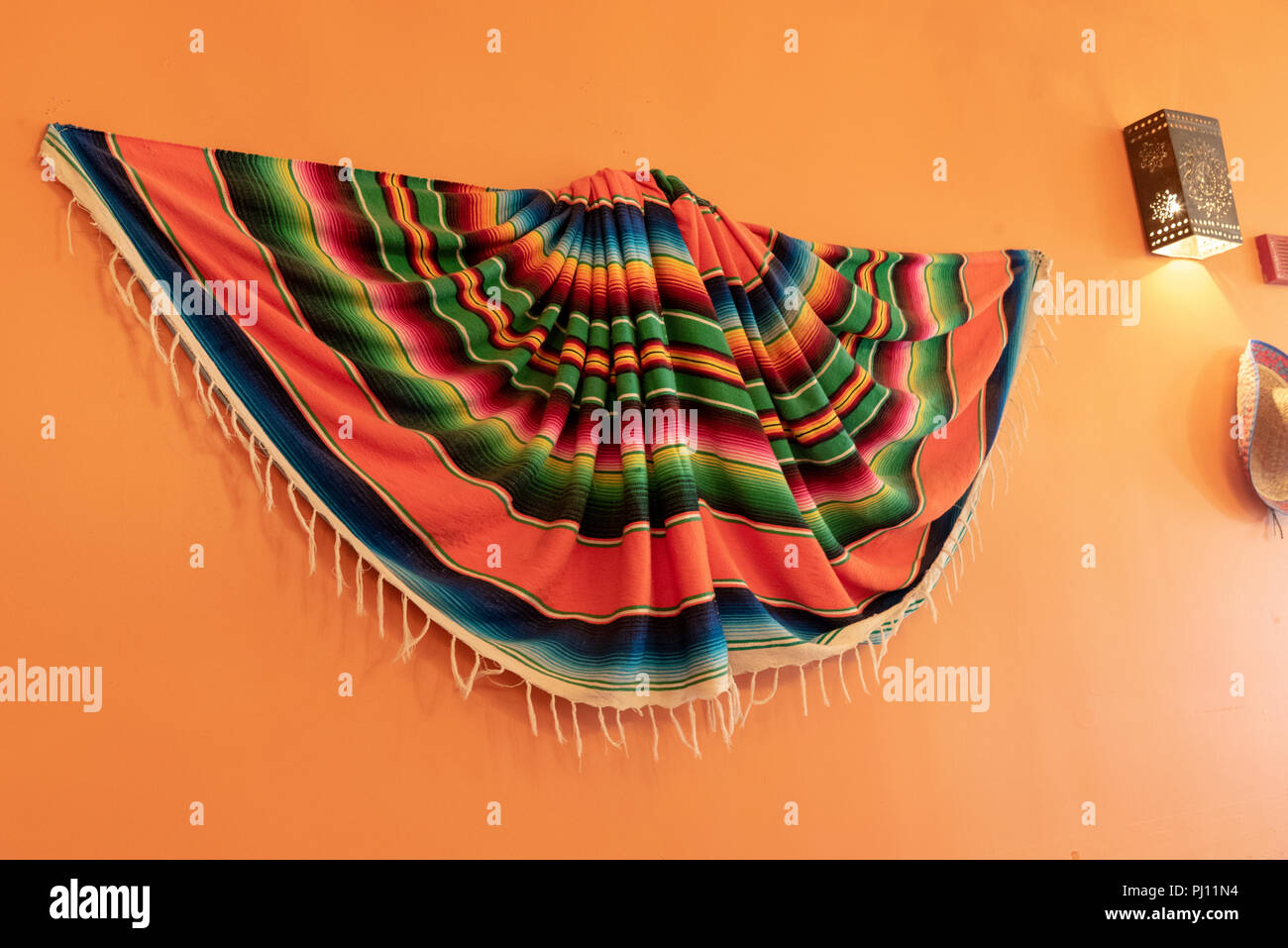 Multicolored poncho hanging on orange wall next to light. - Stock Image