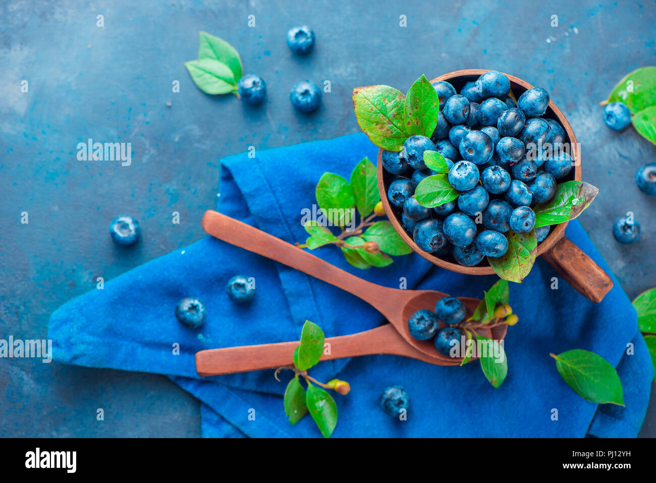 Summer berries flat lay. Blueberries in a ceramic cup with wooden spoons from above. Neutral colors, blue and gray palette, copy space - Stock Image