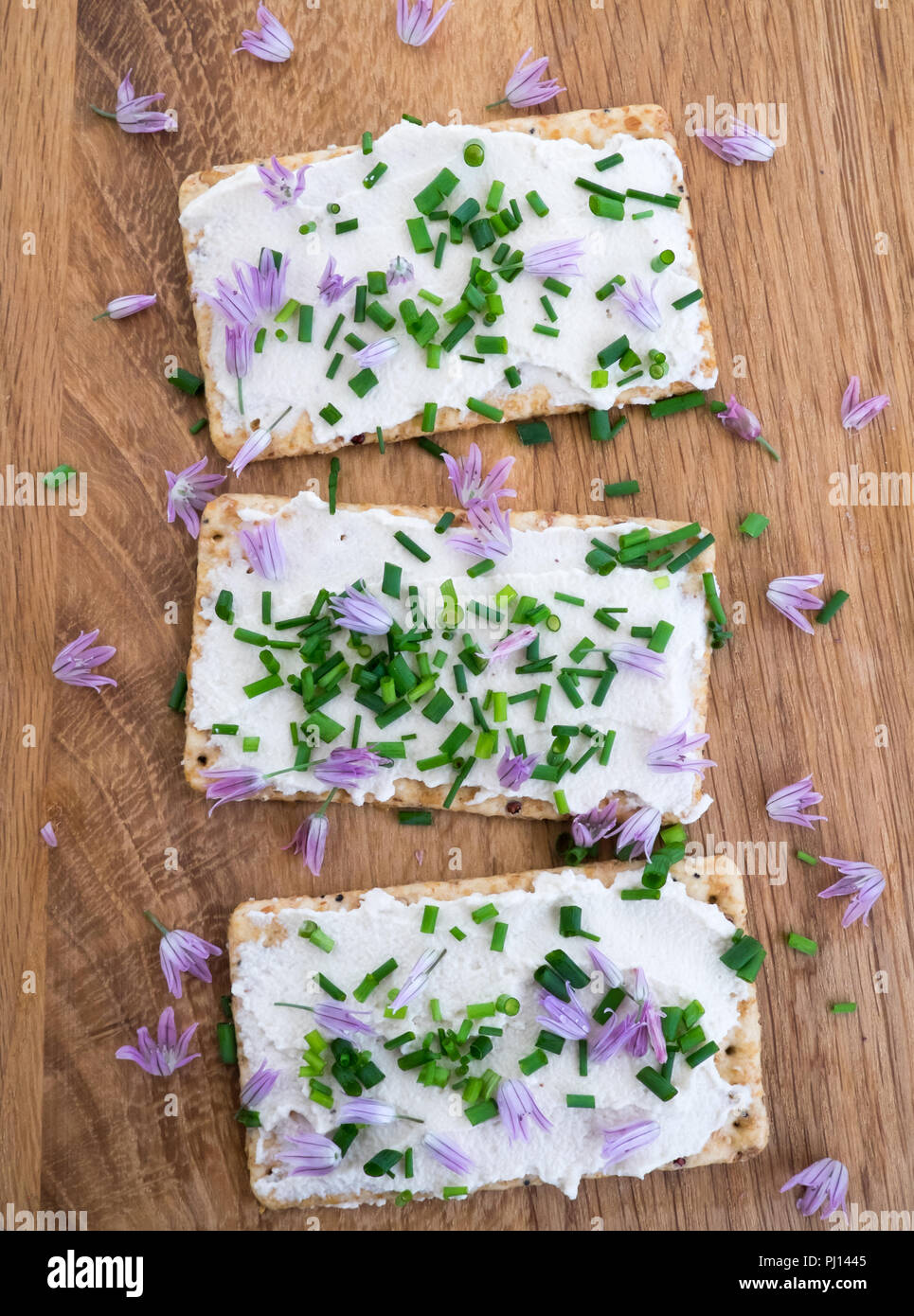 Dairy and lactose-free vegan cream cheese spread made from cashew and macadamia nuts on crackers with fresh chopped chives and edible chive flowers on - Stock Image