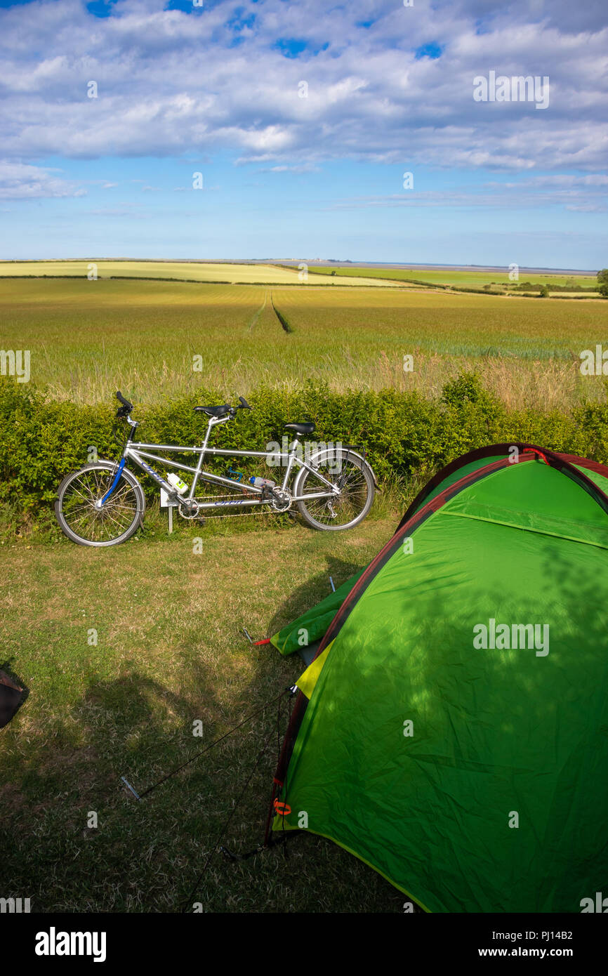 Small tent with a tandem bicycle over looking a field near Beal Northumberland. - Stock Image