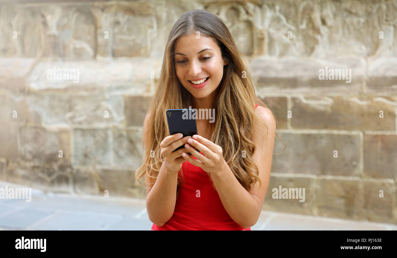 Smiling woman using mobile phone app to play video games online