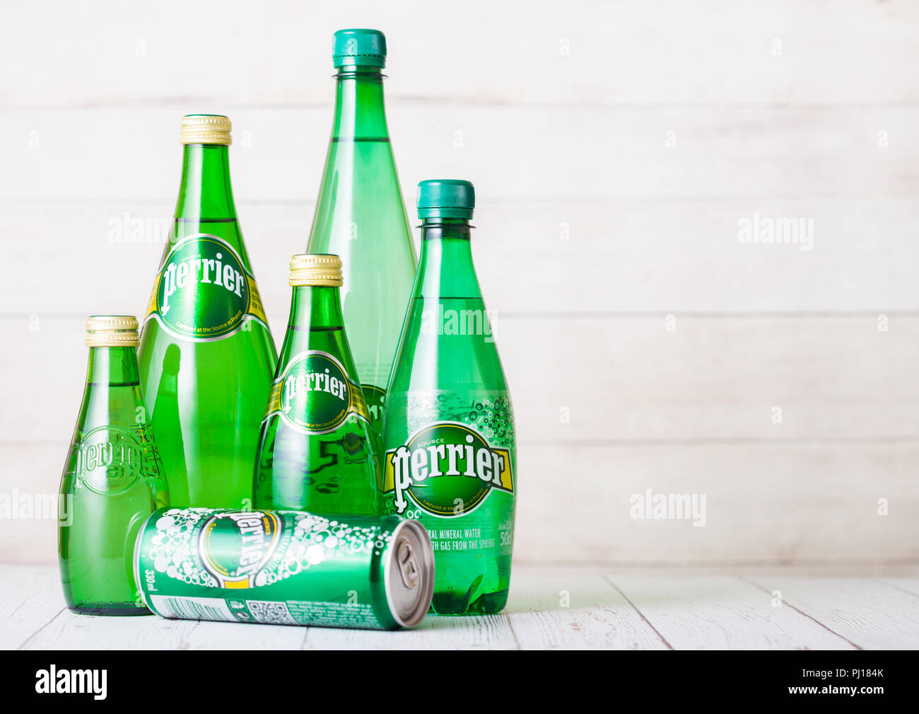 LONDON, UK - SEPTEMBER 03, 2018: Bottles and aluminium tin of Perrier sparkling water on wooden background. Perrier is a French brand of natural bottl - Stock Image