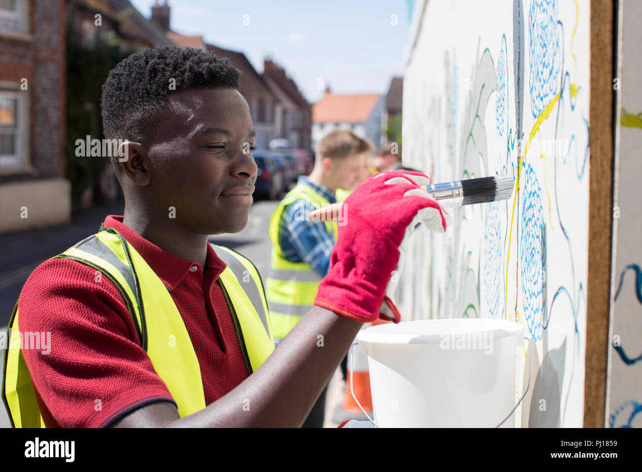 Group Of Helpful Teenagers Creating And Maintaining Community Art Project Stock Photo