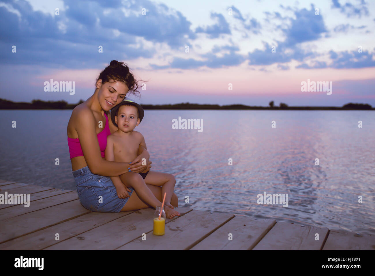 Happy mother with her son enjoy the beautiful sunset while sitting on a wooden pier by the river. Positive human emotions, feelings, joy. Happy family - Stock Image