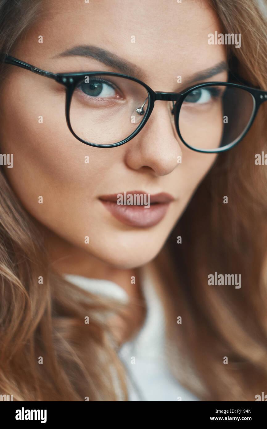 Fashionable eyewear model close-up portrait. Beautiful full lips, eyebrows, transparent glasses with black stylish frame, deep blue eyes, expressive f - Stock Image