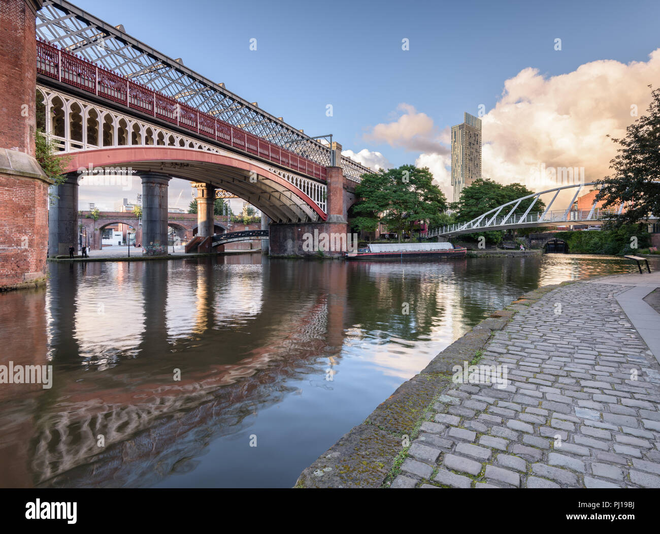 Early morning view from the tow path alongside Bridgewater Canal in Castlefield, Manchester, showing the MSJAR and Merchant's bridges and the Hilton Stock Photo