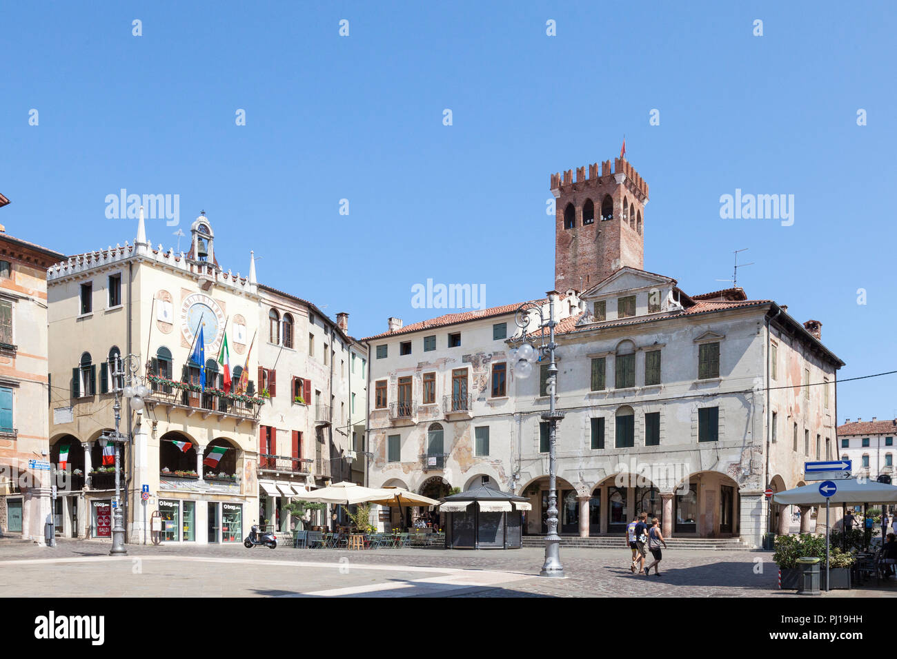 Piazza Liberta, Bassano del grappa, Vicenza, Italy with open air restaurant, wall frescoes and the Civic Tower in the background, blue sky midday - Stock Image