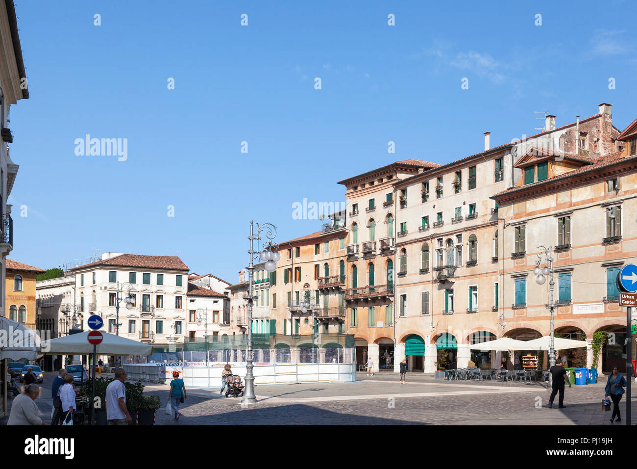 Piazza Liberta, Bassano del Grappa, Vicenza, Italy early morning. Locals going about daily life. Historic architecture. Roller skating rink for school - Stock Image