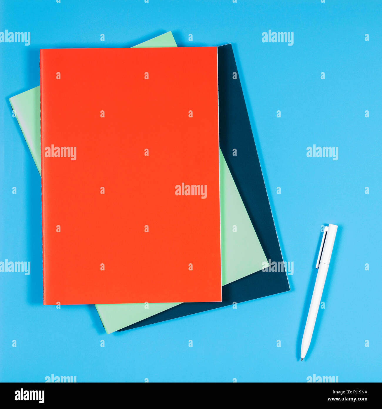 Colorful books notebooks on blue background - Stock Image