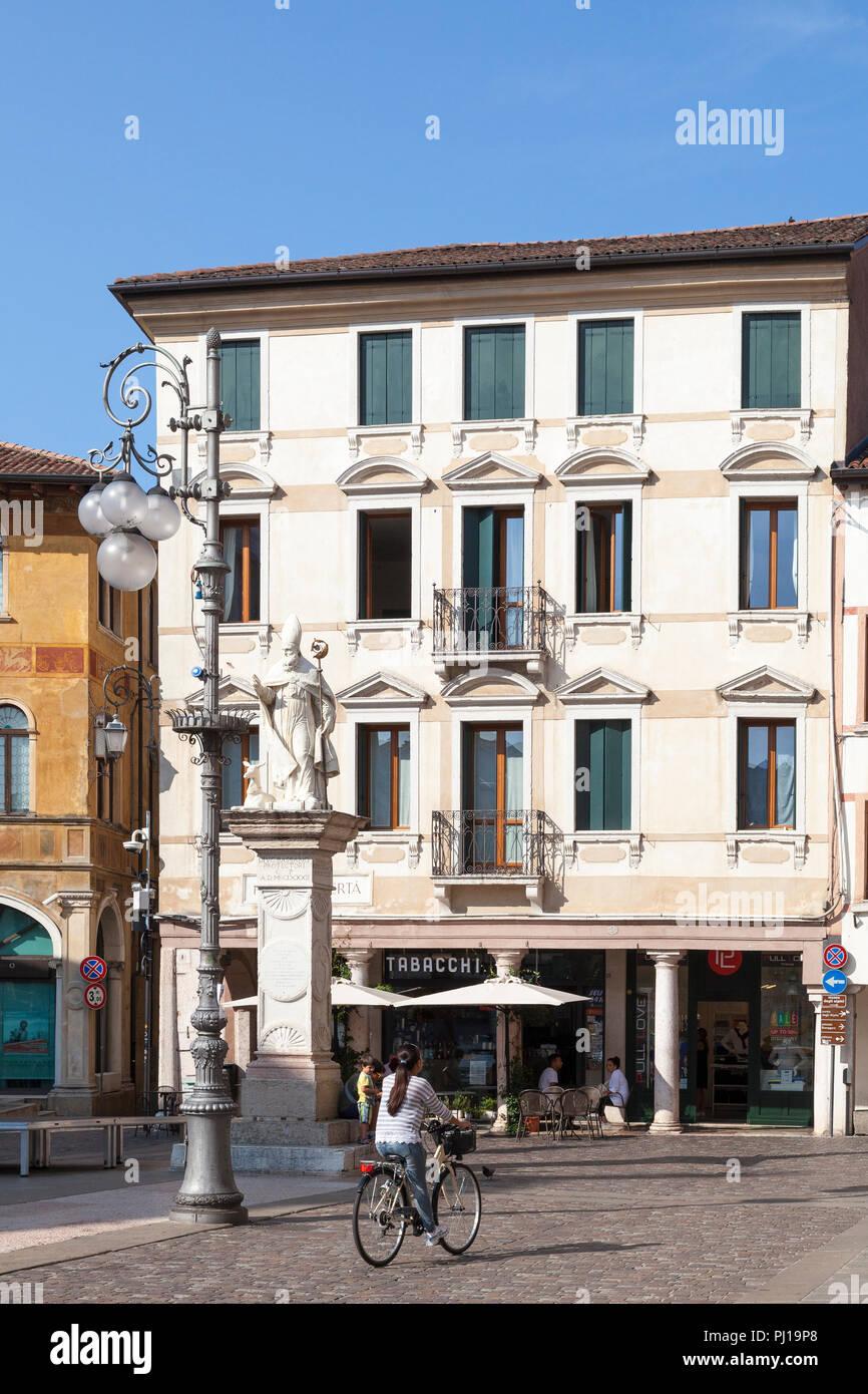 Piazza Liberta, Bassano del Grappa, Vicenza, Italy early morning. Woman cycling cobbled street, ancient architecture. San Bassiano Statue, patron sain - Stock Image