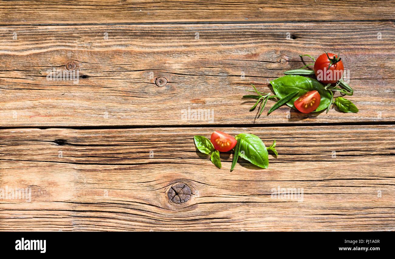 Tomato and basil on rough wood. Stock Photo