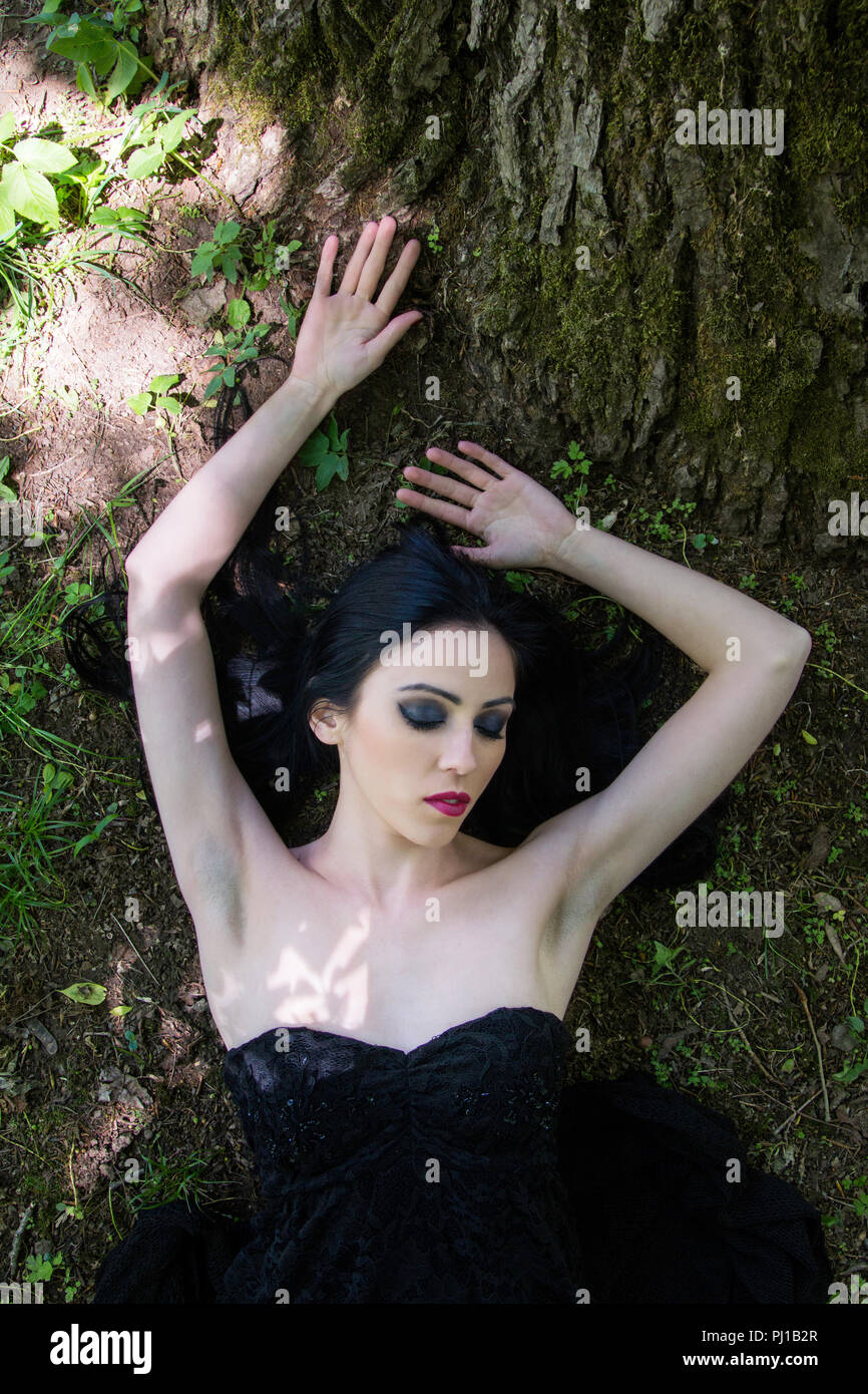 Pale woman in black dress lying on the ground in woods, dark mystery scene - Stock Image