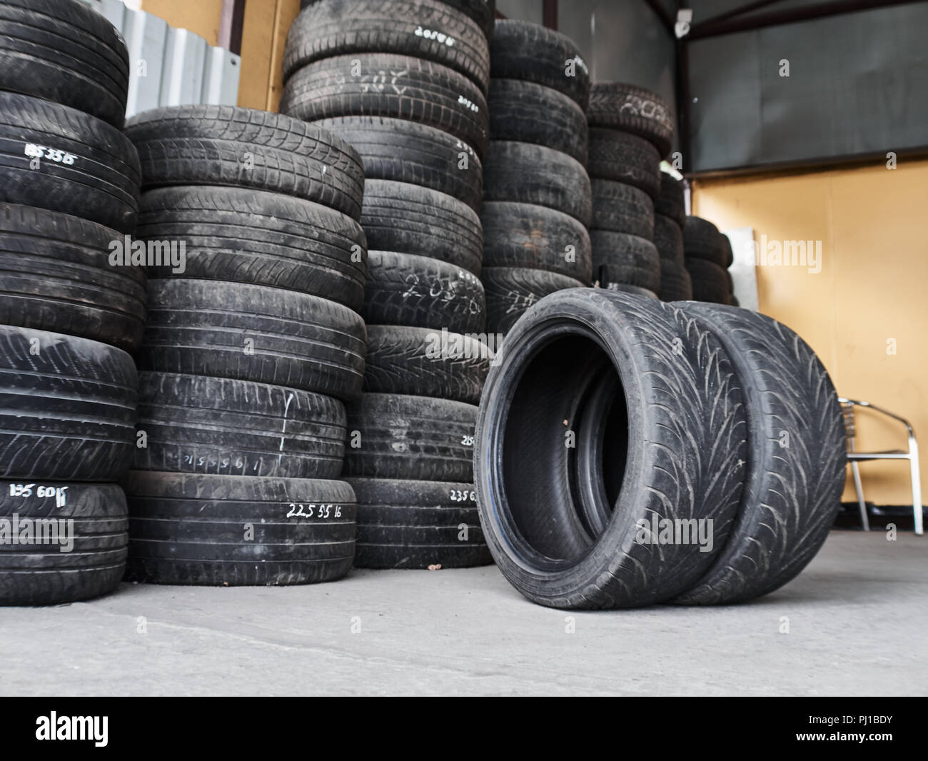 Used car tires stacked in piles at junkyard. Old wheels recycling and utilization concepr - Stock Image
