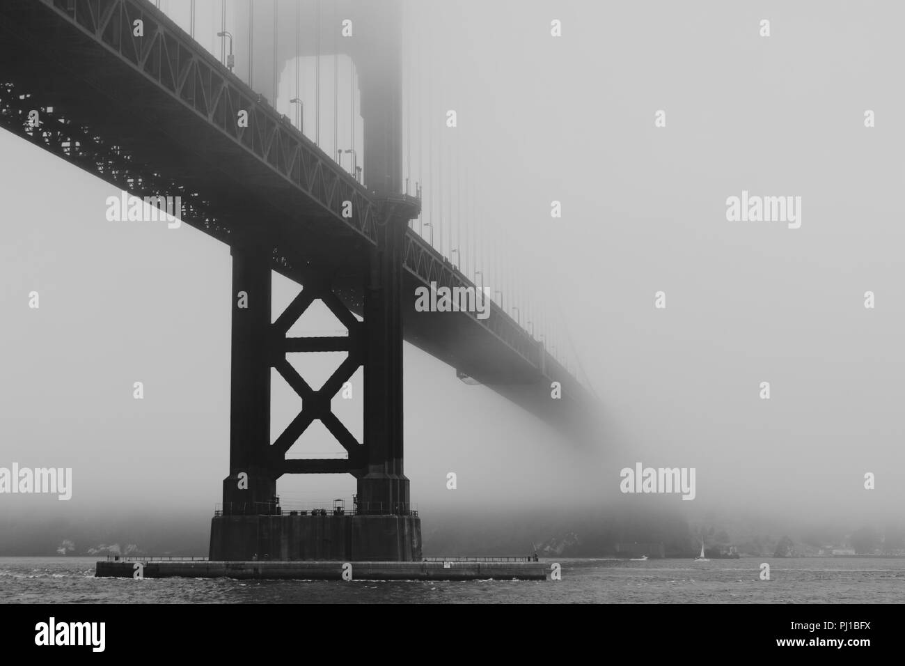 Golden Gate Bridge in the Fog Viewed From Hoppers Hands at Fort Point in Black and White - Stock Image