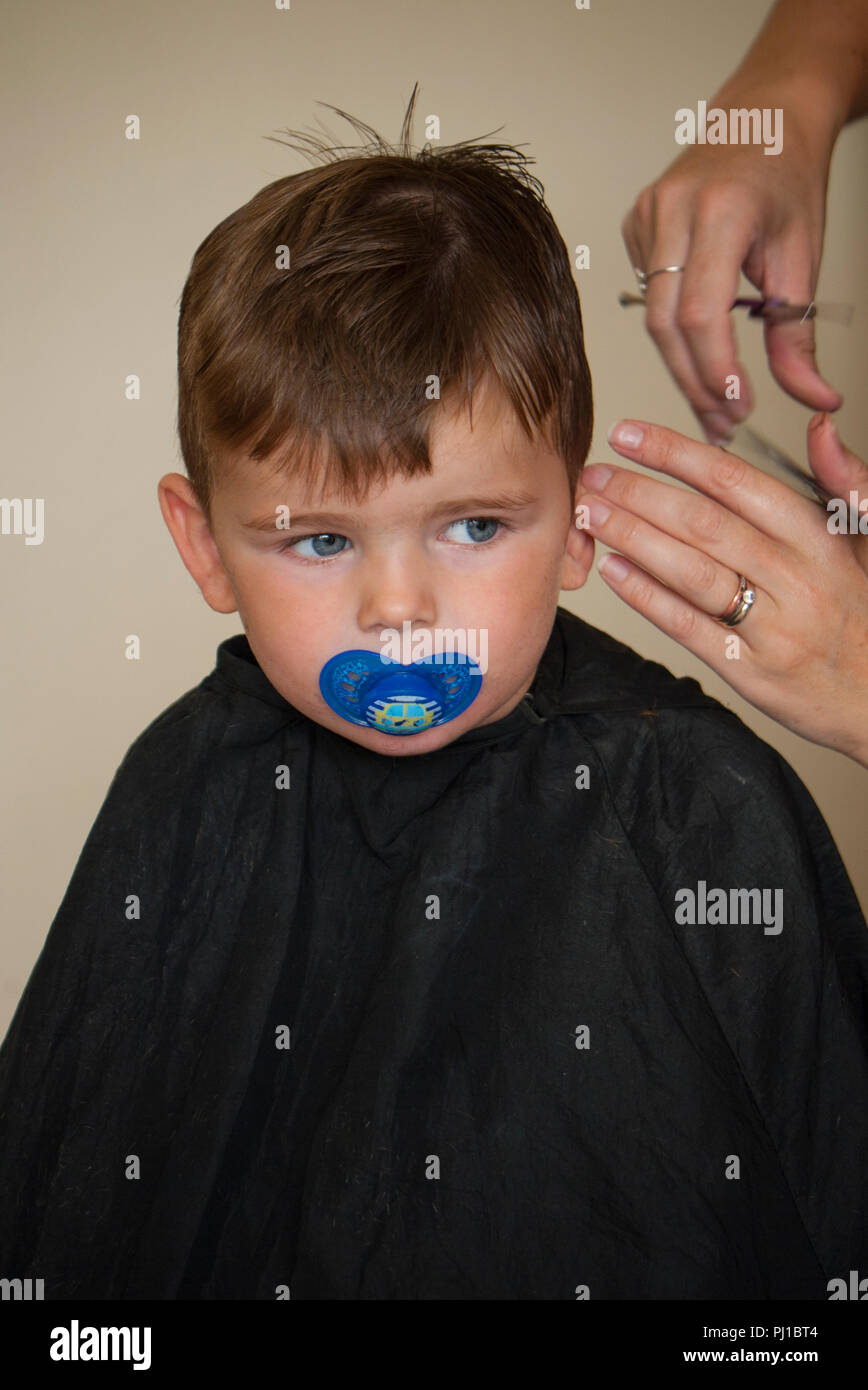Young boy (3 year old) with dummy in mouth having his hair