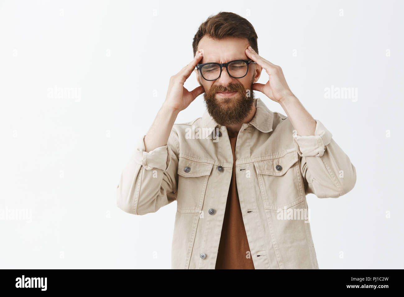Man losing concentration feeling intense being workaholic grimacing from painful feeling in head holding hands on temples closing eyes and smirking suffering from migraine or headache over gray wall - Stock Image