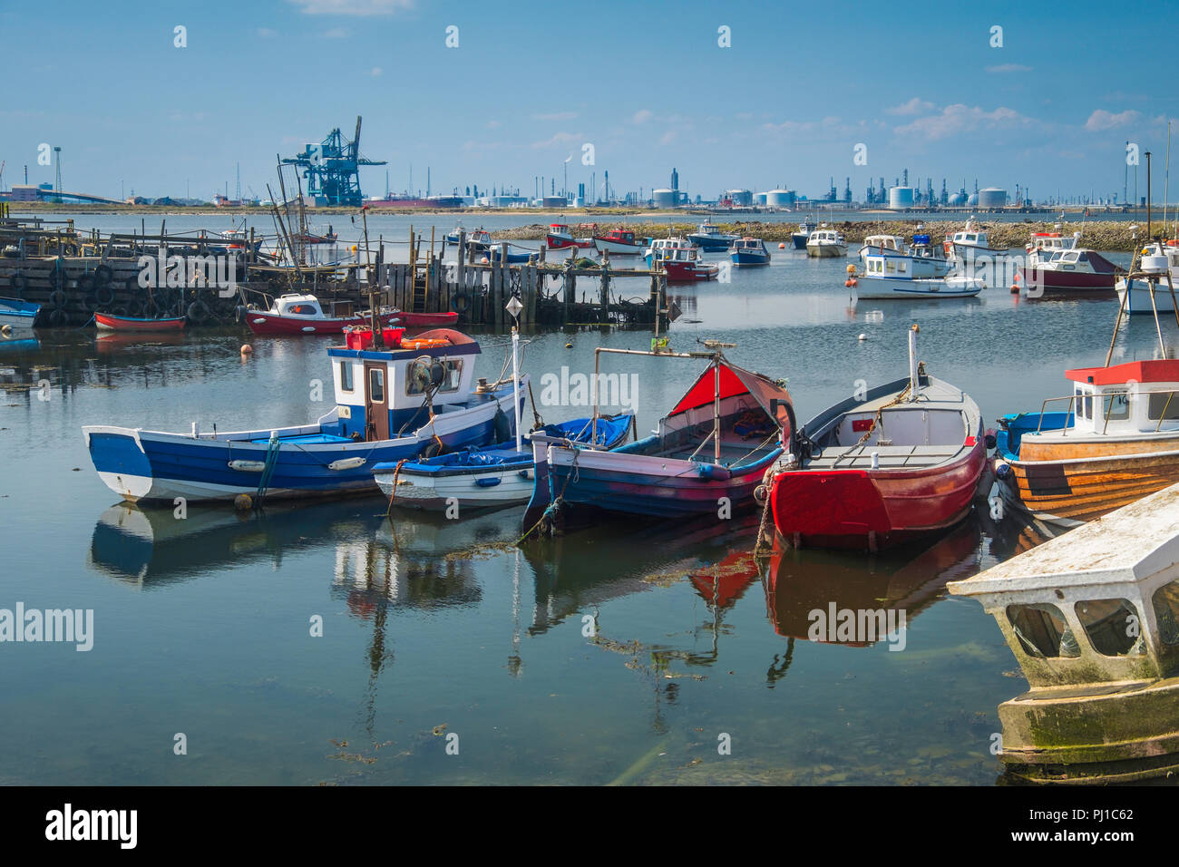 Small fishing boats in Paddys Hole on South Gare with the industrial north bank of the Tees behind. - Stock Image