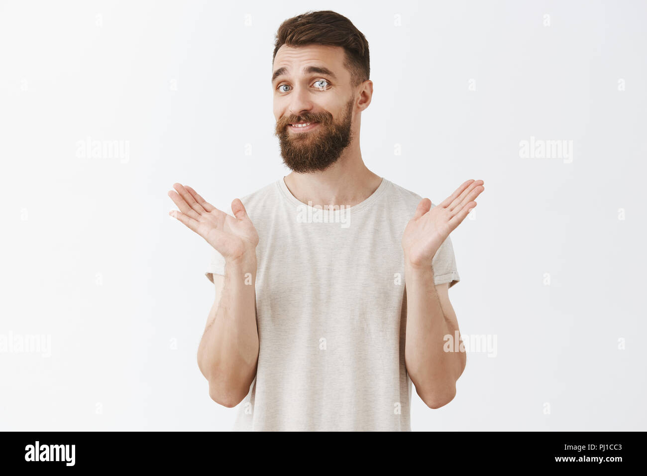 Portrait of tricky careless and stylish handsome male with long hipster beard raising palms and shrugging in unaware gesture having no clue about topic and smiling indifferently over gray background - Stock Image