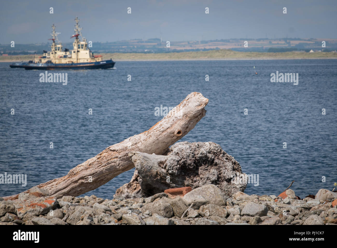 Tugs set out of the Tees past driftwood. - Stock Image