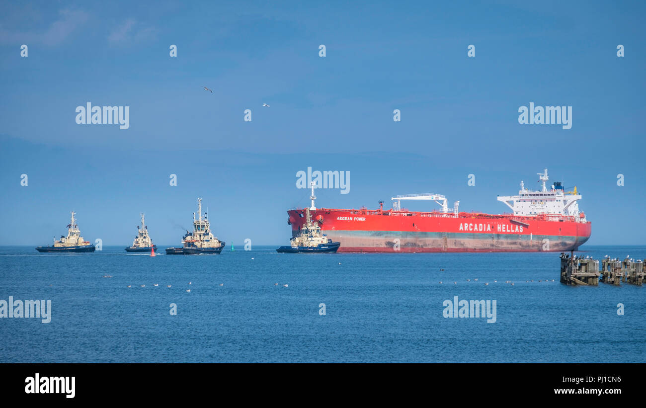The crude oil tanker Aegean Power with a deadweight of 115,754 tons is brought into Seal Sands port by four tugs. - Stock Image